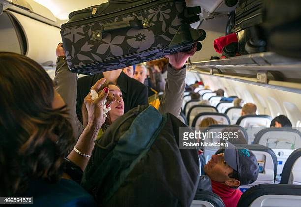 Passengers load their carryon bags into overhead bins on a United Airlines flight March 6 2015 at the Denver International Airport in Denver Colorado