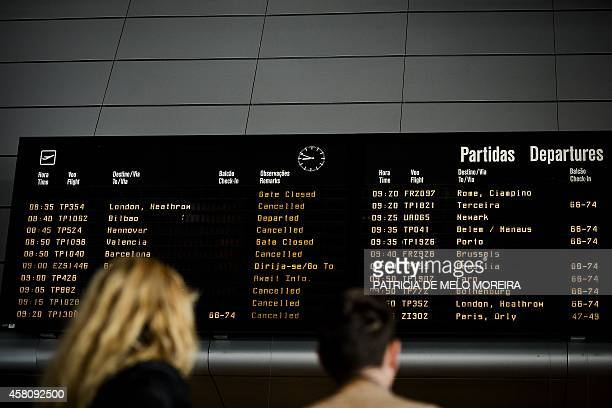 Passengers look at an electronic departures board in the boarding area of Lisbon's airport showing canceled flights during a strike on October 30...