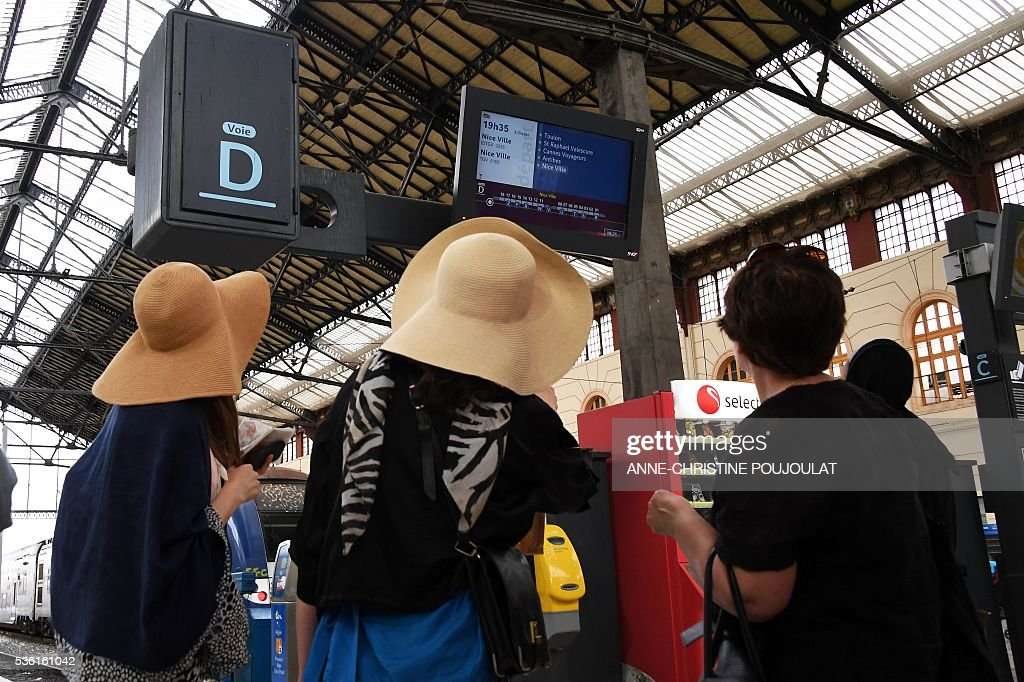 Passengers look at an information screen as they wait for a train in the Saint-Charles rail station in Marseille, southeastern France, on May 31, 2016, at the start of a strike by employees of French state-owned rail operator SNCF to protest against government labour reforms. France is bracing for a week of severe disruption to transport after unions called for more action in their bitter standoff with the Socialist government over its labour market reforms. / AFP / ANNE