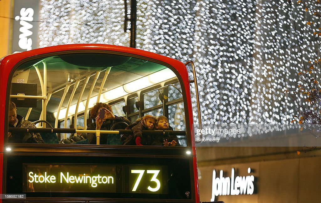 Passengers look at Christmas lights from the upper-deck of a London Bus as it passes the John Lewis Plc department store on Oxford Street in London, U.K., on Monday, Dec. 17, 2012. Retailers are relying on Christmas sales to help rescue a year when high unemployment and the debt crisis have blighted spending. Photographer: Simon Dawson/Bloomberg via Getty Images