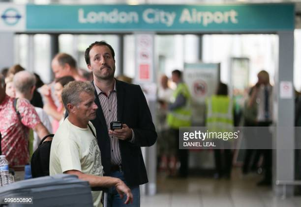 Passengers look at departure screens at London City Airport in London after protestors blocked the runway and caused all the flights from the airport...