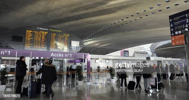 Passengers look at departures screens on February 7 2012 at the Paris international airport of RoissyCharles de Gaulle Flights were cancelled today...