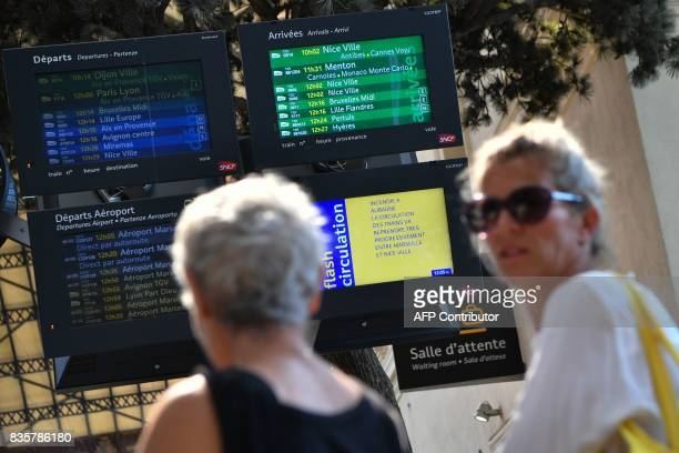 Passengers look at information monitors as they wait for their trains at The SaintCharles Station in Marseille on August 20 following a fire between...