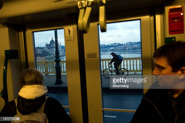 Passengers look at the city skyline through the window of a tram as it crosses a bridge over the Danube river in Budapest Hungary on Tuesday Jan 17...