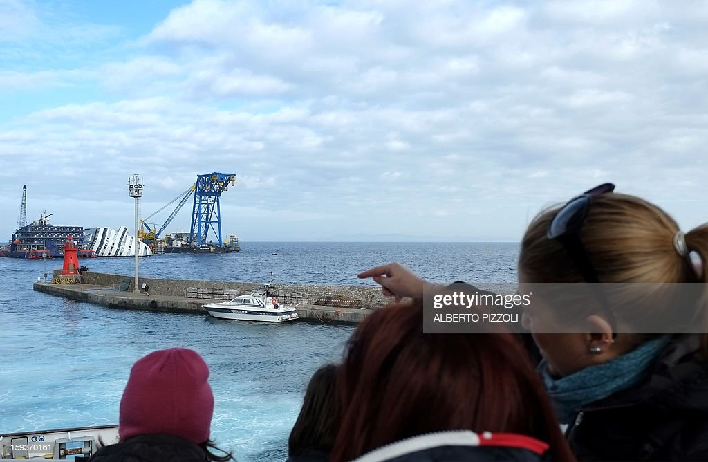 Passengers look at the Costa Concordia cruise ship from the ferryboat on January 12, 2013 on the Italian island of Isola del Giglio. A year on from the Costa Concordia tragedy in which 32 people lost their lives, the giant cruise ship still lies keeled over on an Italian island.
