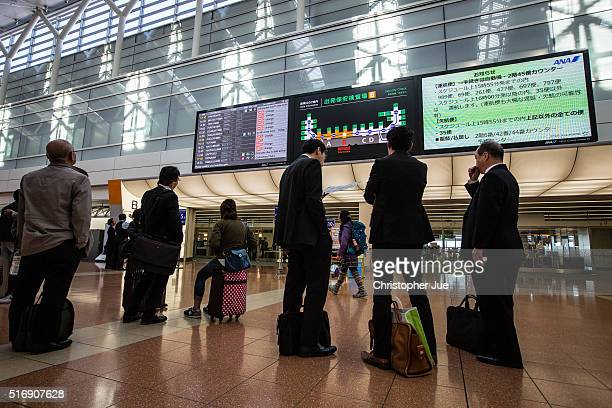 Passengers look at the flight departures indicator board which shows several All Nippon Airways flights delayed and cancelled at Haneda Airport on...