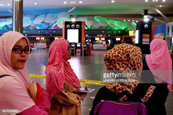 Passengers look on as Malaysia's Hazmat team cordon off an area inside the departures terminal for a decontamination operation at the Kuala Lumpur...