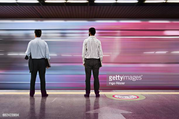 Passengers looking at subway train entering the station at high speed
