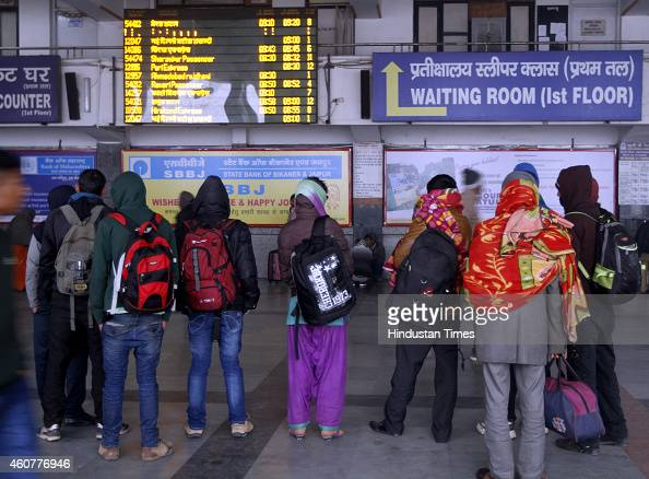 Passengers looking at train schedule at New Delhi Railway Station on a chilly morning on December 22 2014 in New Delhi India Dense fog reduced...