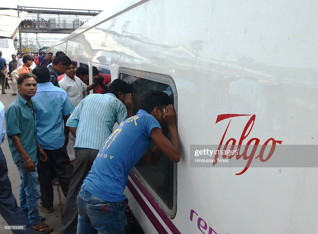 Passengers looking inside Spanish train Talgo at Bareily railway station during its first trial run between Bareilly and Moradabad on May 29, 2016 in Bareilly, India. The trial of Spanish train Talgo, the lighter and faster vehicle with speed up to 115 km per hour, was conducted between Bareilly and Moradabad in Uttar Pradesh as part of the Railways' strategy to increase the speed of trains. Nine Talgo coaches were hauled by a 4,500 HP diesel engine on the 90-km line for the first trial run.
