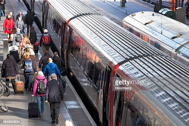 Passengers make their way along a railway platform as they prepare to board an Virgin Trains East Coast train operated by Virgin Trains before its...
