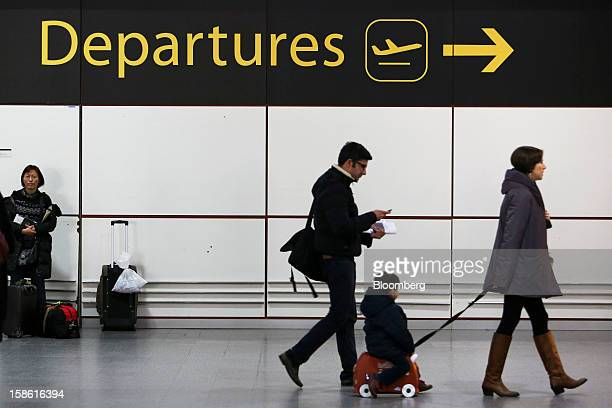 Passengers make their way towards the departures area of the north terminal at Gatwick airport in Crawley UK on Friday Dec 21 2012 UK airports...