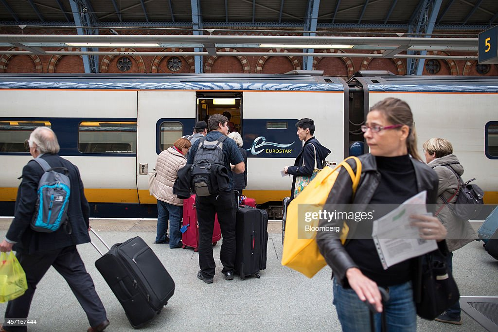 Passengers move their luggage along a platform before boarding a Eurostar train operated by Eurostar International Ltd ahead of departure from St...