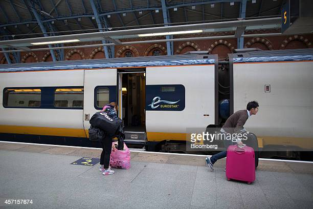 Passengers move their luggage along the platform before boarding a Eurostar train operated by Eurostar International Ltd ahead of departure from St...
