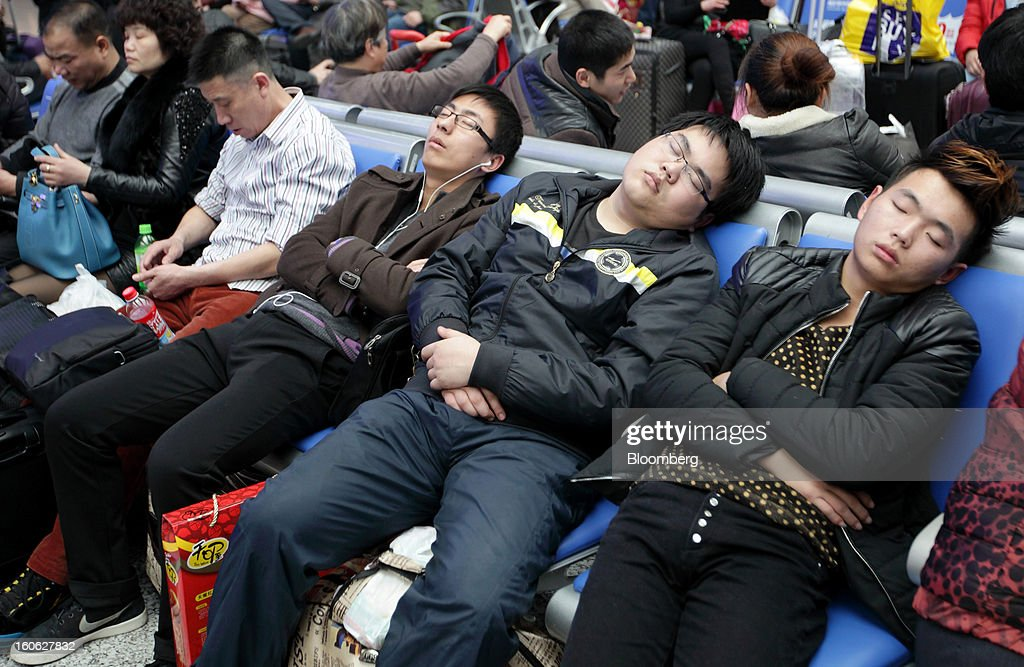 Passengers nap as they wait to board trains at Hongqiao Railway Station in Shanghai, China, on Sunday, Feb. 3, 2013. Forecasts of snow and rain across China threaten to disrupt the travel plans of millions of Chinese heading home for the Lunar New Year holidays that start Feb. 9, the national weather agency warned. Photographer: Tomohiro Ohsumi/Bloomberg via Getty Images