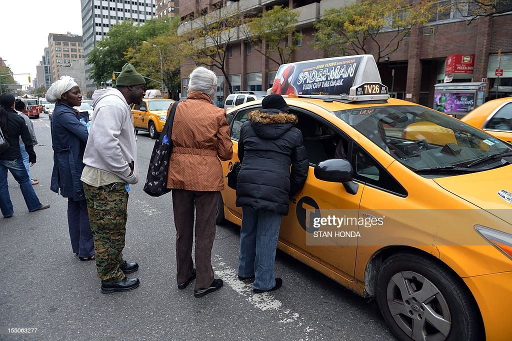 Passengers negociate with a taxi driver on First Avenue October 31, 2012 in New York. Yellow cabs were allowed to pick up multiple fares due to limited public transportation as a result of Hurricane Sandy. AFP PHOTO/Stan HONDA