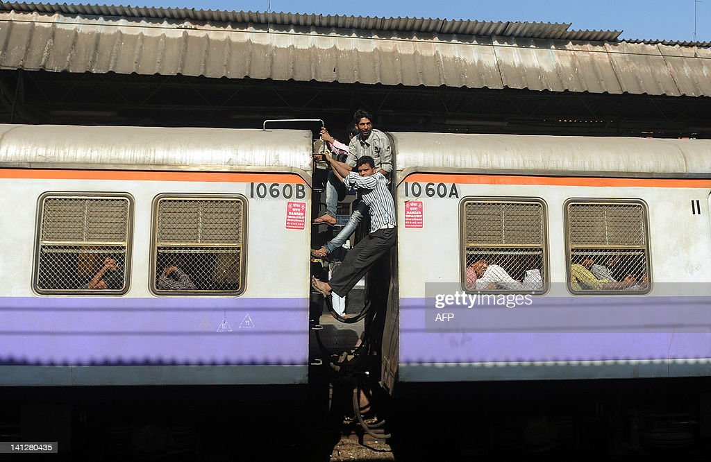 Passengers occupy the space between two train compartments of an overcrowded train in Mumbai on March 14, 2012. Indian Railways Minister Dinesh Trivedi presents the railway budget for the fiscal year to March 2012-13 in Parliament on March 14. Pitching for expansion of rail infrastructure, minister Trivedi may allocate significant funds while presenting the budget for Dedicated Freight Corridors (DFC) to expedite its execution. The railway, the country's largest employer with some 1.4 million people on its payroll, runs 11,000 passenger and freight trains and carries 19 million people daily. AFP PHOTO/Punit PARANJPE