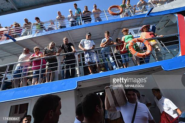 Passengers of a ship which transports locals tourist and various goods are pictured at the harbor of the Crisan village in the heart of the Danube...