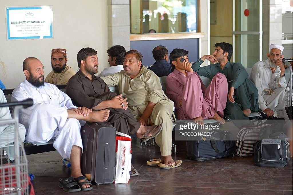 Passengers of Karachibound Pakistan International Airline flights wait after delays at the Benazir Bhutto International Airport in Islamabad on June...