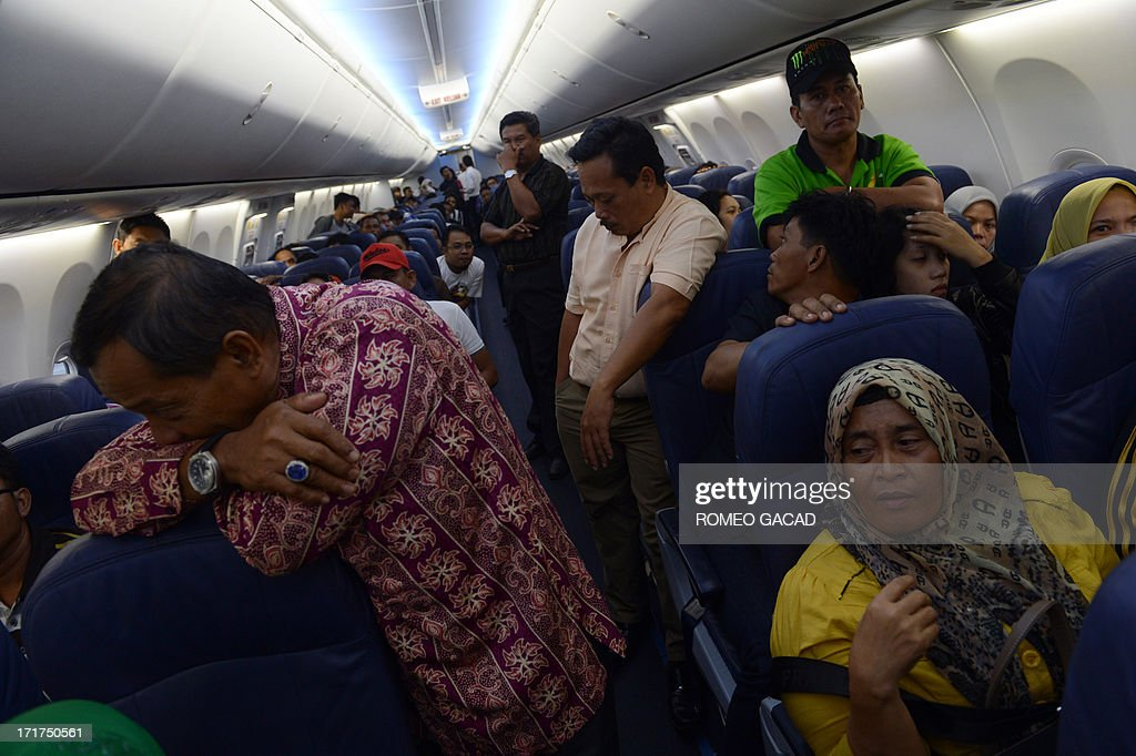 Passengers of Lion Air Indonesia's domestic airline flight 292 from Jakarta to Pekanbaru city wait inside the plane at Batam airport on June 28, 2013 where the plane was temporarily diverted by airport authorities due to heavy blanket of haze at Pekanbaru airport. The flight was delayed for several hours until the visibility improved while haze from forest fire continue to blanket Riau province located in Sumatra island. Thousands of firefighters are tackling the blazes in Riau province and have been helped in recent days by heavy rain. Officials said the number of fire hotspots detected late June 26, 2013 had fallen to just six from 265 the previous day.