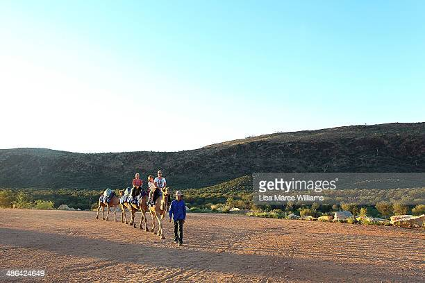 Passengers of The Ghan ANZAC Tribute train ride camels during a visit to a old quarry in the isolated East MacDonnell Ranges for a outback bush bbq...