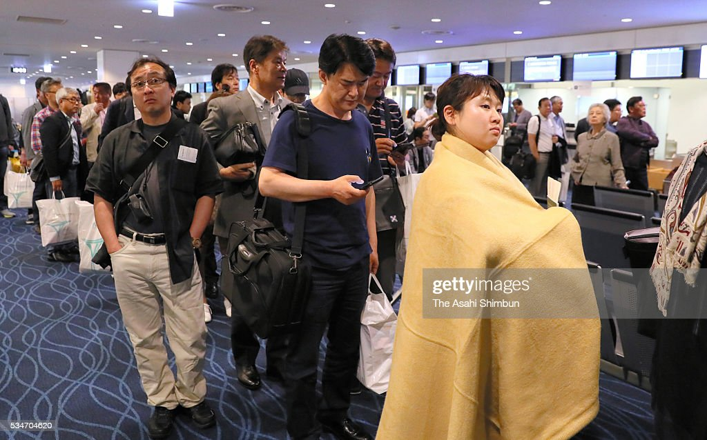 Passengers of the Korean Air 2708 bound for Seoul queue to get an alternative airplane after the fire at the Haneda International Airport on May 27, 2016 in Tokyo, Japan. 319 passengers and crews have safely evacuated.