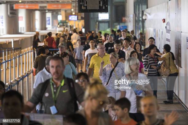 Passengers of the Ovation of the Seas Quantumclass cruise ship operated by Royal Caribbean Cruises Ltd exit the Kai Tak Cruise Terminal in Hong Kong...