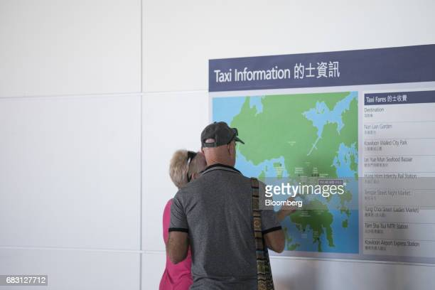 Passengers of the Ovation of the Seas Quantumclass cruise ship operated by Royal Caribbean Cruises Ltd look at a taxi information board at the Kai...