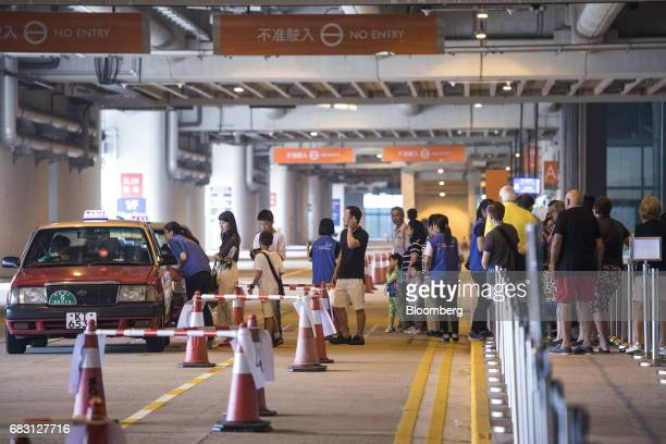 Passengers of the Ovation of the Seas Quantumclass cruise ship operated by Royal Caribbean Cruises Ltd stand in line at a taxi stand at the Kai Tak...