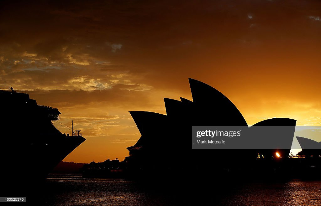 Passengers on a cruise ship look towards the Sydney Opera House sails at sunrise on December 16 2014 in Sydney Australia Sydney siege gunman Man...
