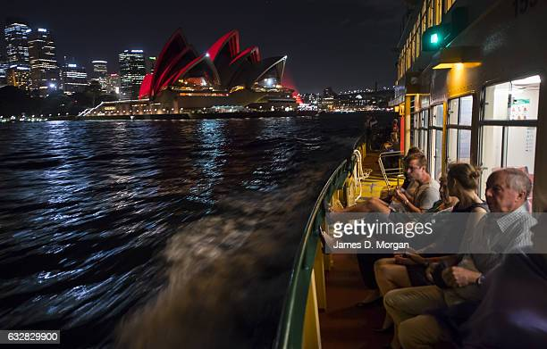 Passengers on an evening ferry watch the Opera House lit red on January 27 2017 in Sydney Australia A number of events are being held across Sydney...