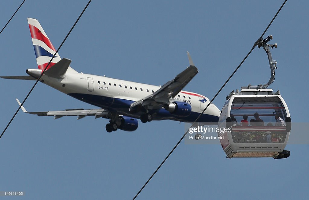 Passengers on The Emirates Air Line cable car (R) get a close up view as a passenger jet comes into land at London City Airport on July 21, 2012 in London, England.