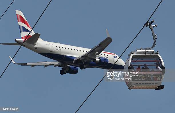 Passengers on The Emirates Air Line cable car get a close up view as a passenger jet comes into land at London City Airport on July 21 2012 in London...