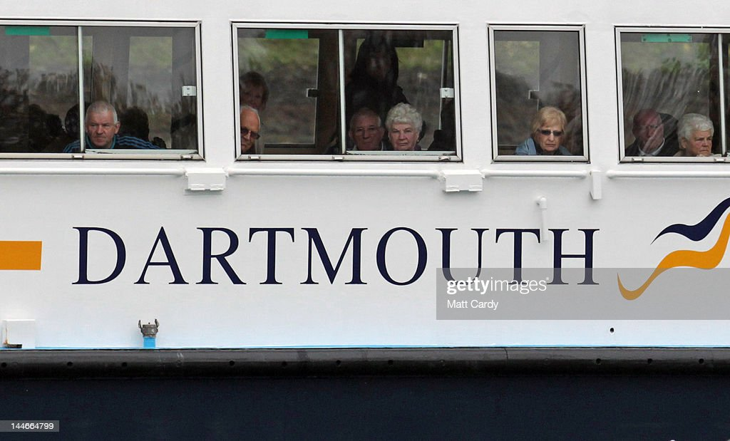 Passengers on the ferry Dart Explorer watch as Royal Navy vessels that have been training at the Britannia Royal Naval College substitute it for the...