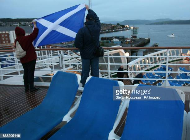 Passengers on the QE2 brave the early morning cold to watch the Liner dock in Greenock near Glasgow where she was built 40 years ago The ship is on a...