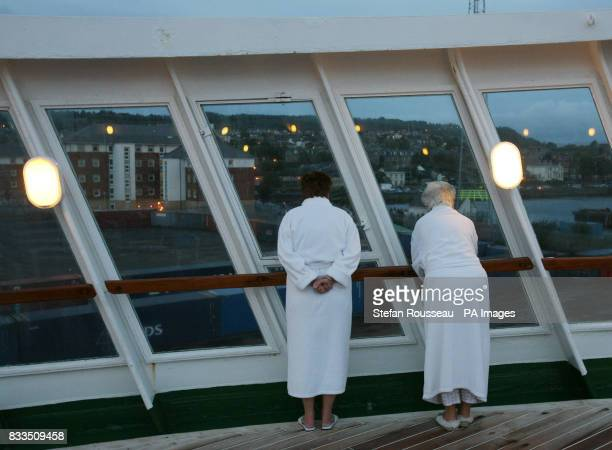 Passengers on the QE2 brave the early morning cold to watch the Liner dock in Greenock near Glasgow where she was built 40 years ago