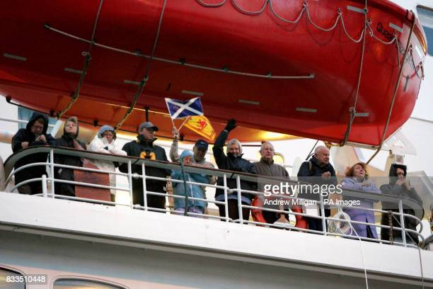 Passengers on the QE2 wave as the Liner docks in Greenock near Glasgow