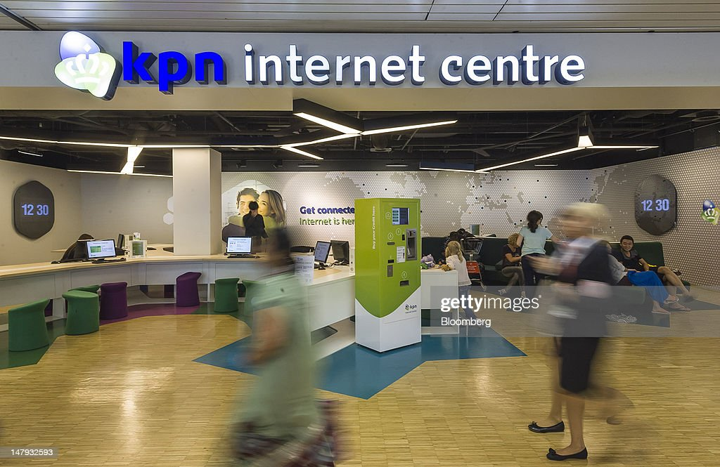 Passengers pass a Royal KPN NV internet centre at Schiphol airport in Amsterdam, Netherlands, on Friday, July 6, 2012. America Movil SAB, Mexican billionaire Carlos Slim's wireless carrier, won the 28 percent stake it sought in Royal KPN NV, increasing its influence in Europe even after opposition from the Dutch operator. Photographer: Jock Fistick/Bloomberg via Getty Images