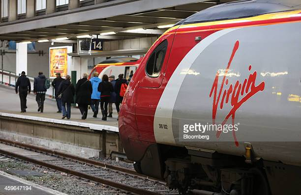 Passengers pass a West Coast train operated by Virgin Trains as it stands beside a platform at Euston railway station in London UK on Thursday Nov 27...