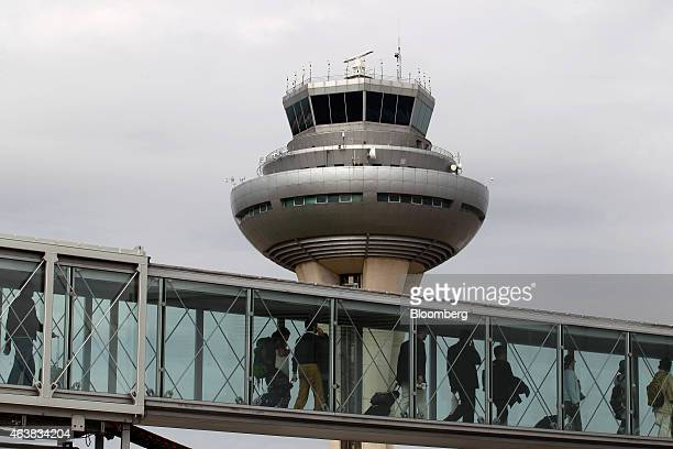 Passengers pass along a gangway as the control tower stands beyond at Madrid Barajas airport operated by Aena SA in Madrid Spain on Wednesday Feb 18...