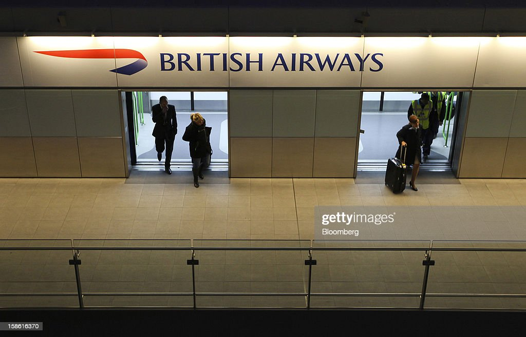 Passengers pass beneath a British Airways advertisement as they disembark a terminal transfer train in the north terminal at Gatwick airport in Crawley, U.K., on Friday, Dec. 21, 2012. U.K. airports predicted today to be the busiest day during the Christmas period, as some Britons opt to spend the holidays abroad and overseas visitors fly out to be with friends and family. Photographer: Chris Ratcliffe/Bloomberg via Getty Images
