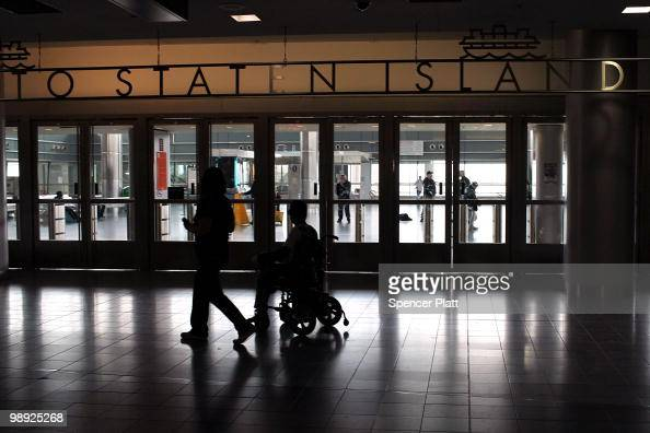 Passengers pass the entrtance to the Staten Island Ferry following the crash of the Staten Island Ferry into a dock in the city's borough of Staten...