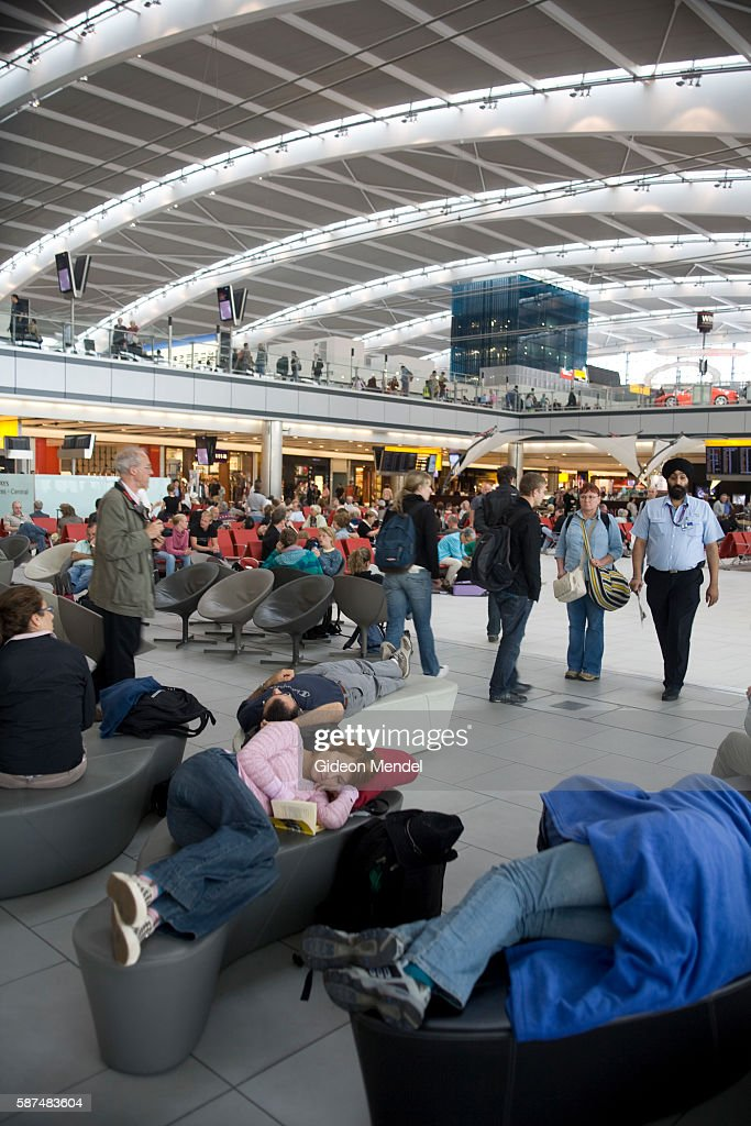 Passengers pass the time as they wait for their flights at the new Heathrow Terminal 5 building This departure hall has an architecturally...
