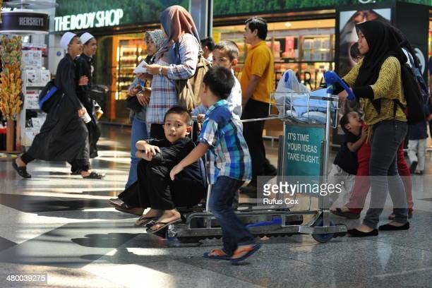 Passengers pass through the departures terminal of Kuala Lumpur International Airport on March 22 2014 in Kuala Lumpur Malaysia The search for...