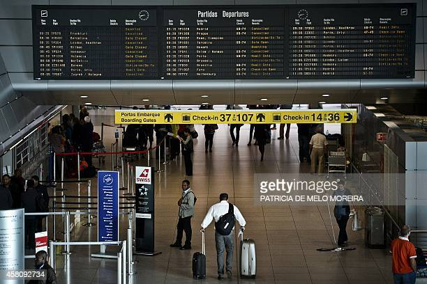 Passengers pass under a electronic departures board in the boarding area of Lisbon's airport showing canceled flights during a strike on October 30...