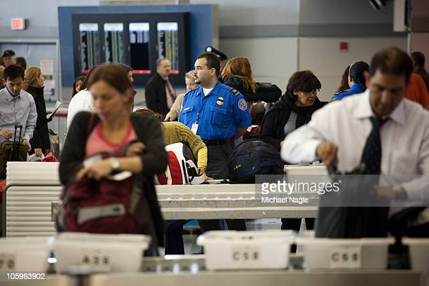 Passengers place their belongings in bins before passing through the passenger security checkpoint at John F Kennedy International Airport's Terminal...