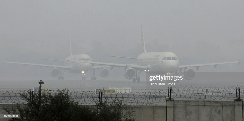 Passengers planes waits at the Runway to take off in dense fog on January 3, 2013 in New Delhi, India. A cold wave is sweeping across north India sending temperatures plunging. Delhi Wednesday witnessed the coldest day in the past 44 years.