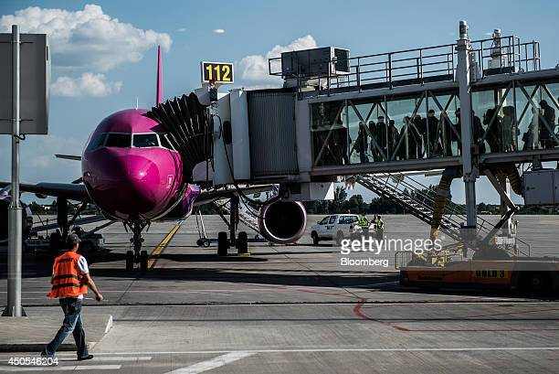 Passengers prepare to board a Wizz Air Ltd aircraft at Henri Coanda International airport in Bucharest Romania on Thursday June 12 2014 For Romania...