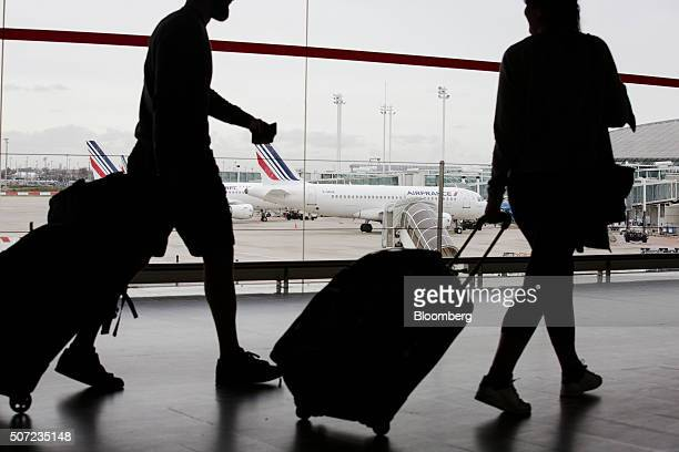 Passengers pull their luggage inside a terminal building as an Air France aircraft operated by Air FranceKLM Group stand on the tarmac beyond at...