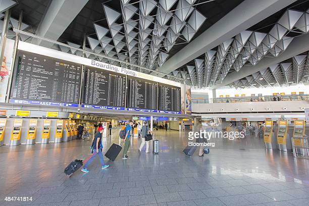 Passengers pull their luggage inside terminal 1 of Frankfurt Airport operated by Fraport AG in Frankfurt Germany on Friday Aug 21 2015 The Greek...